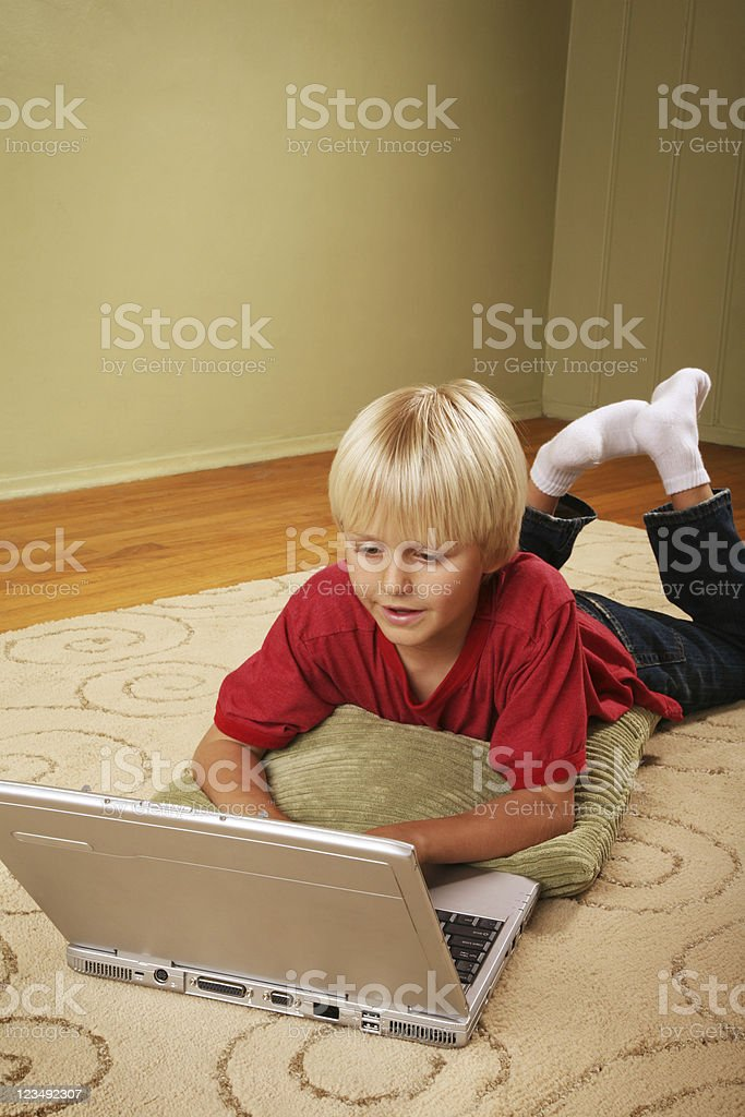 nine year old boy typing on laptop computer stock photo