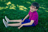 Nine year old cerebral palsy boy sitting in grass field.