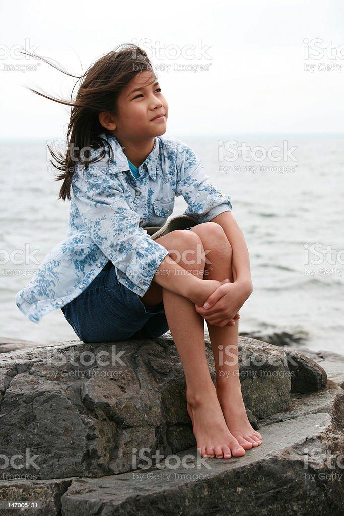 Nine year old girl sitting by lake royalty-free stock photo