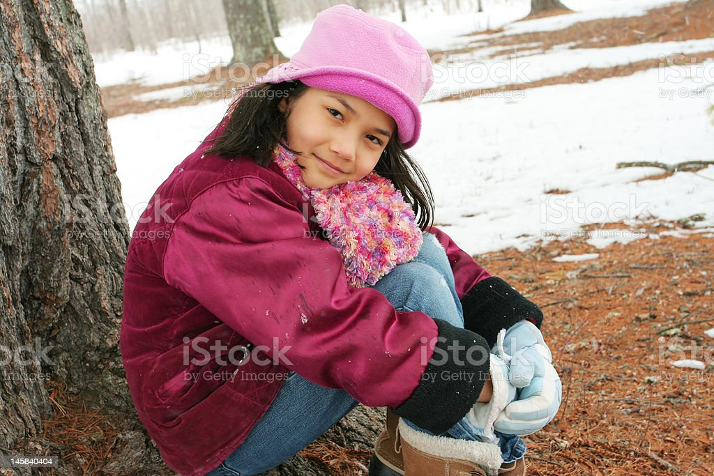 Nine year old girl sitting outdoors in winter royalty-free stock photo