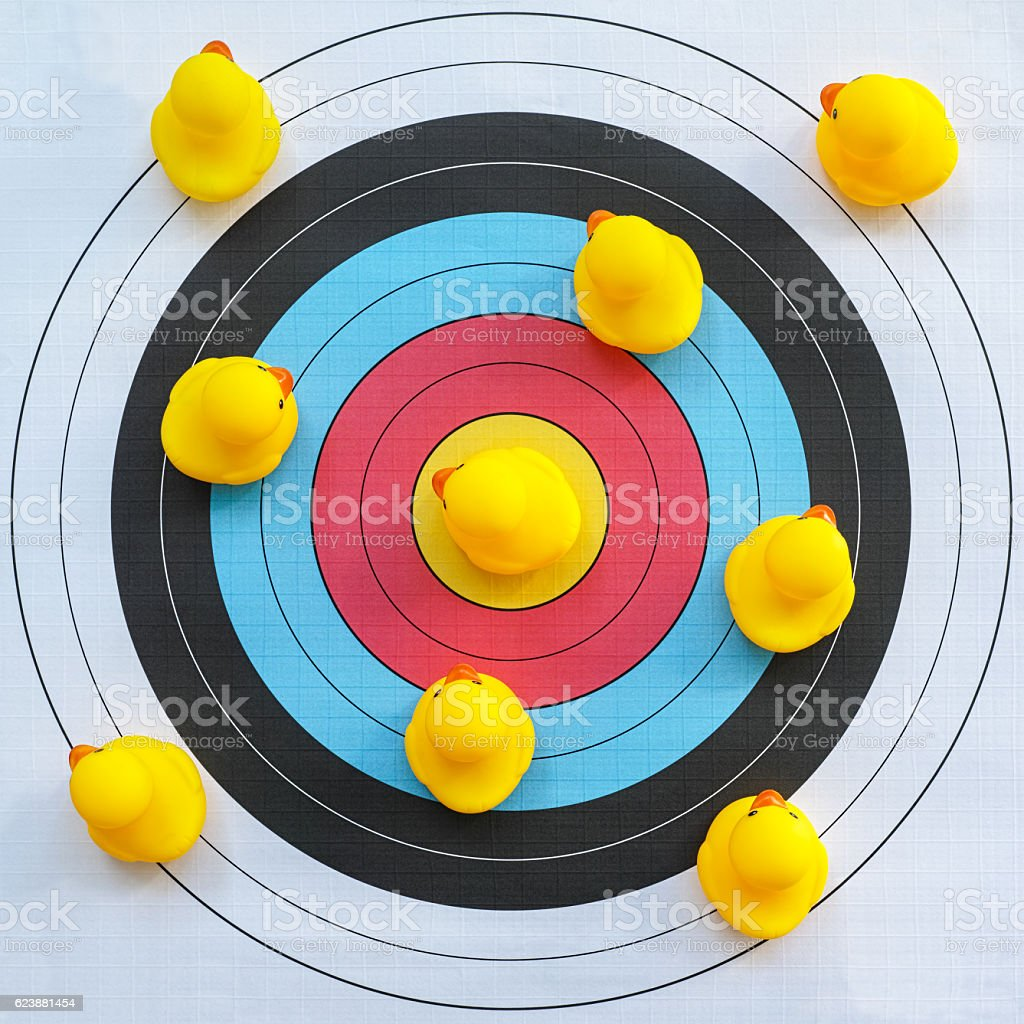 Nine yellow rubber ducks on a target. stock photo