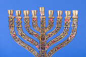 Nine-branched menorah isolated on blue background