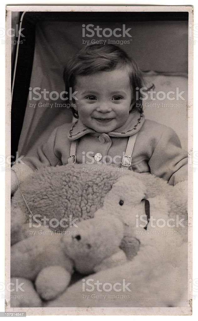 Nineteen forties baby in pram, with teddy bear stock photo