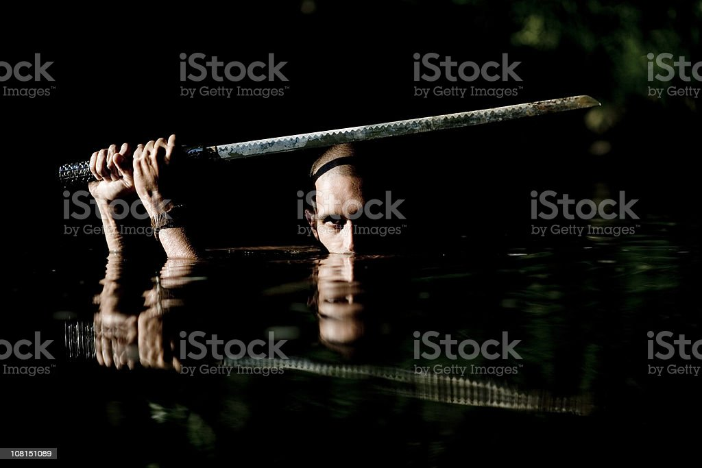 Ninja Holding Sword Above Head and Wading Through Water stock photo