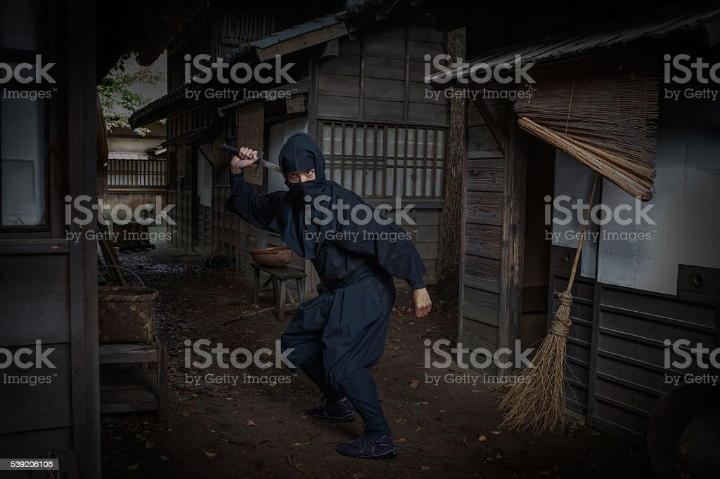 Ninja in Dark, Traditional Japanese Street Pulling Out Sword stock photo