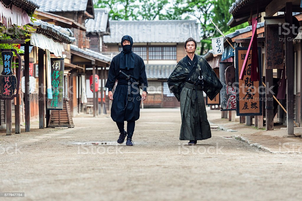 Ninja, Samurai walk in the middle of a village street stock photo