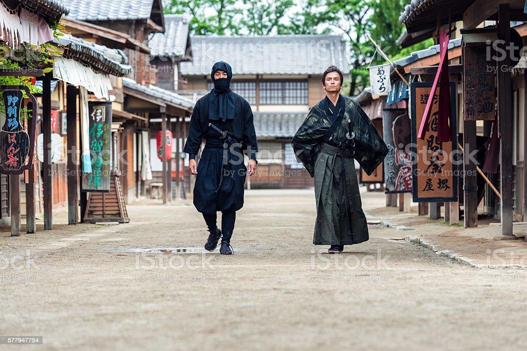 Ninja, Samurai walk in the middle of a village street stock photo