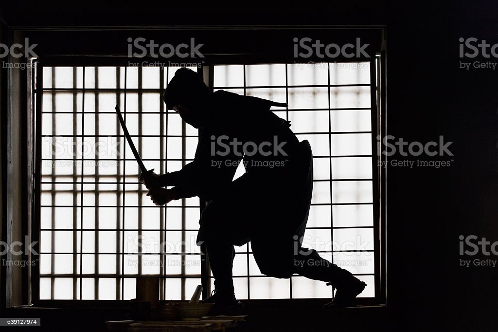 Ninja with Sword Silhouette Against a Window in Japanese House stock photo