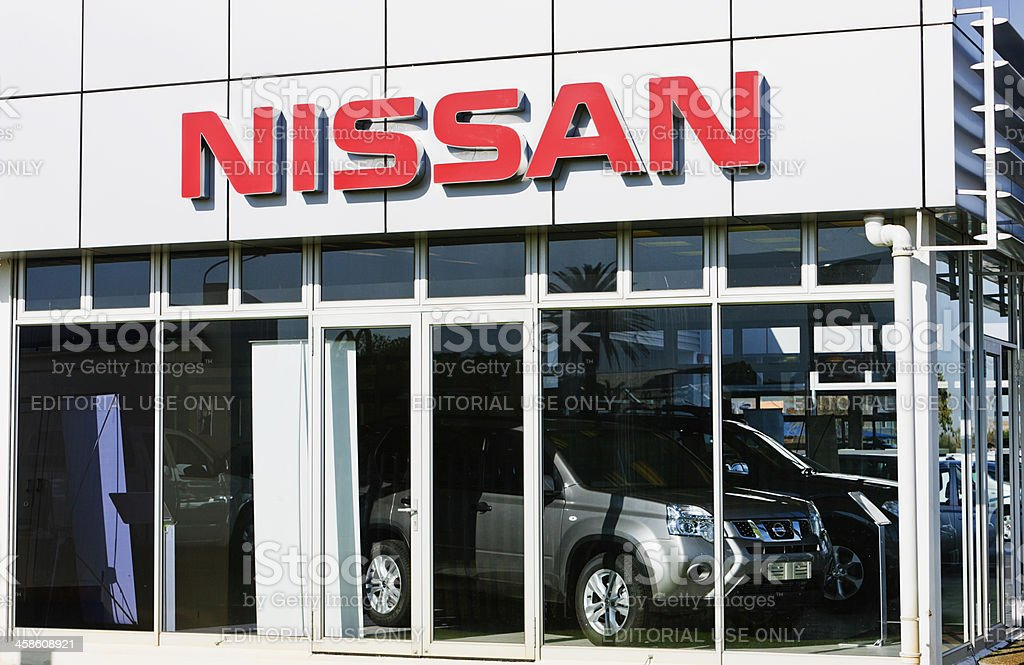 Nissan sign and SUVs at car dealership showroom stock photo