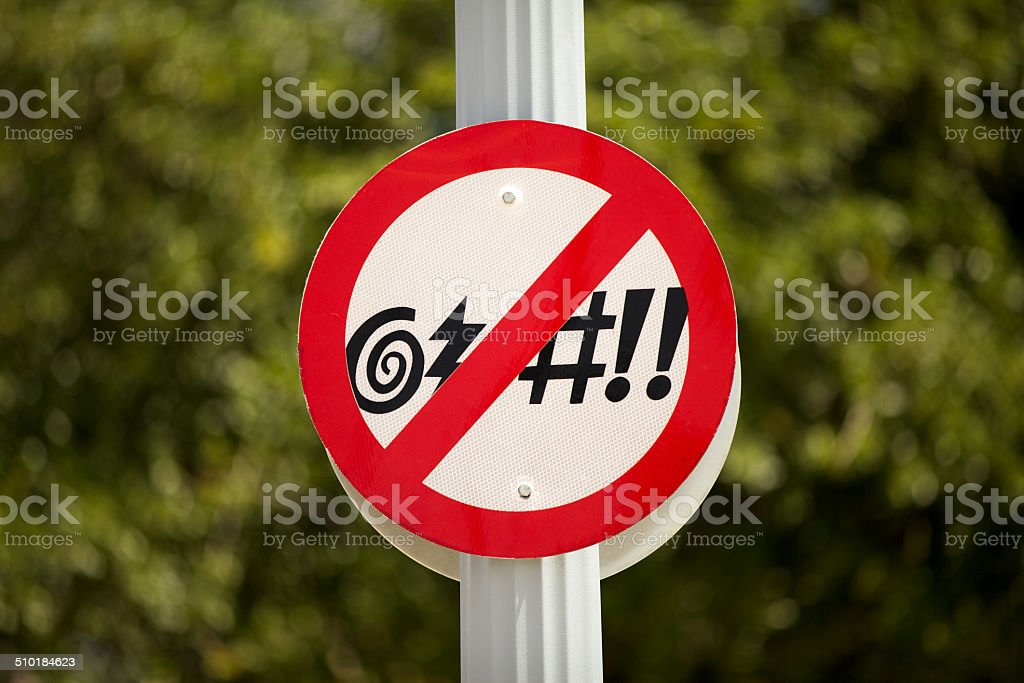 No Cursing Street Sign in front of a green bush stock photo