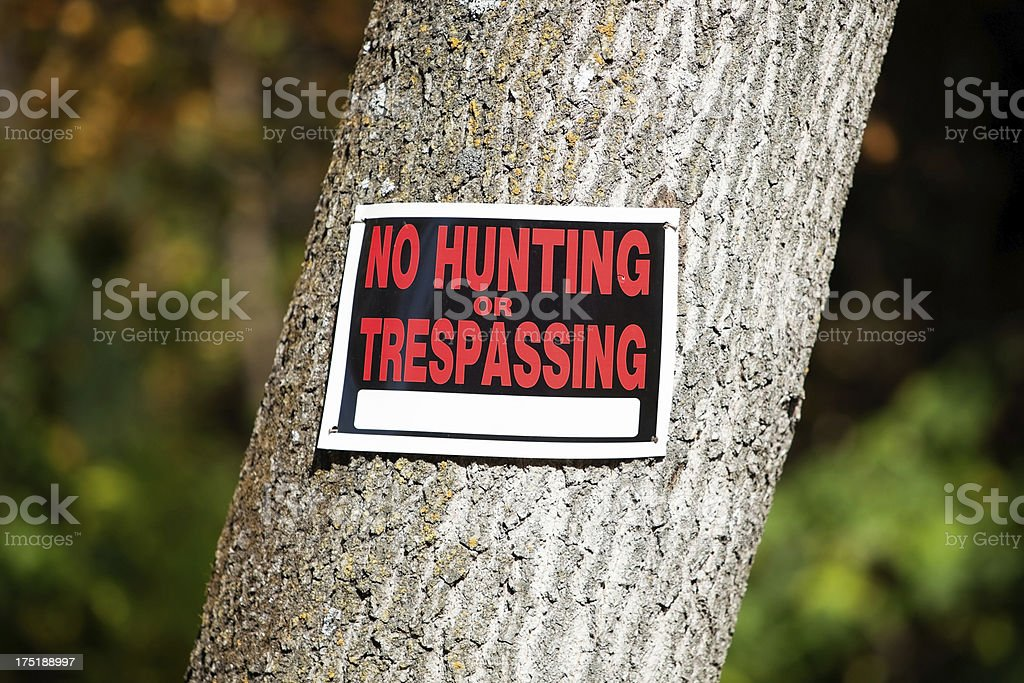 No Hunting or Trespassing sign on Tree Trunk stock photo