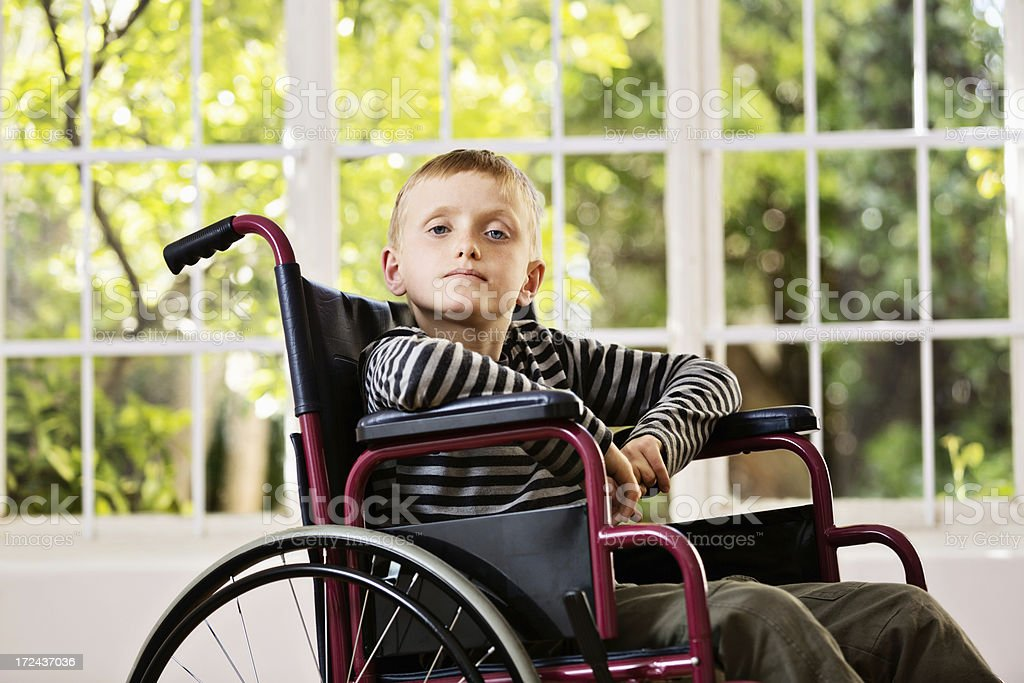 No, it's not fun, but I'm coping. Brave wheelchair boy stock photo