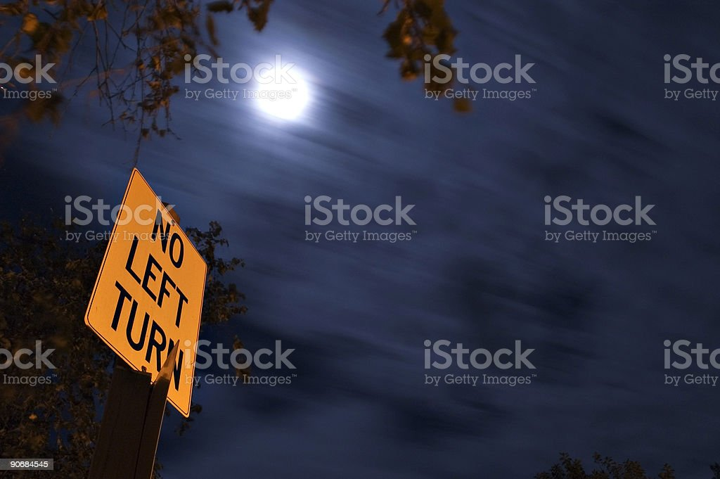 No left turn signage with moon in background stock photo