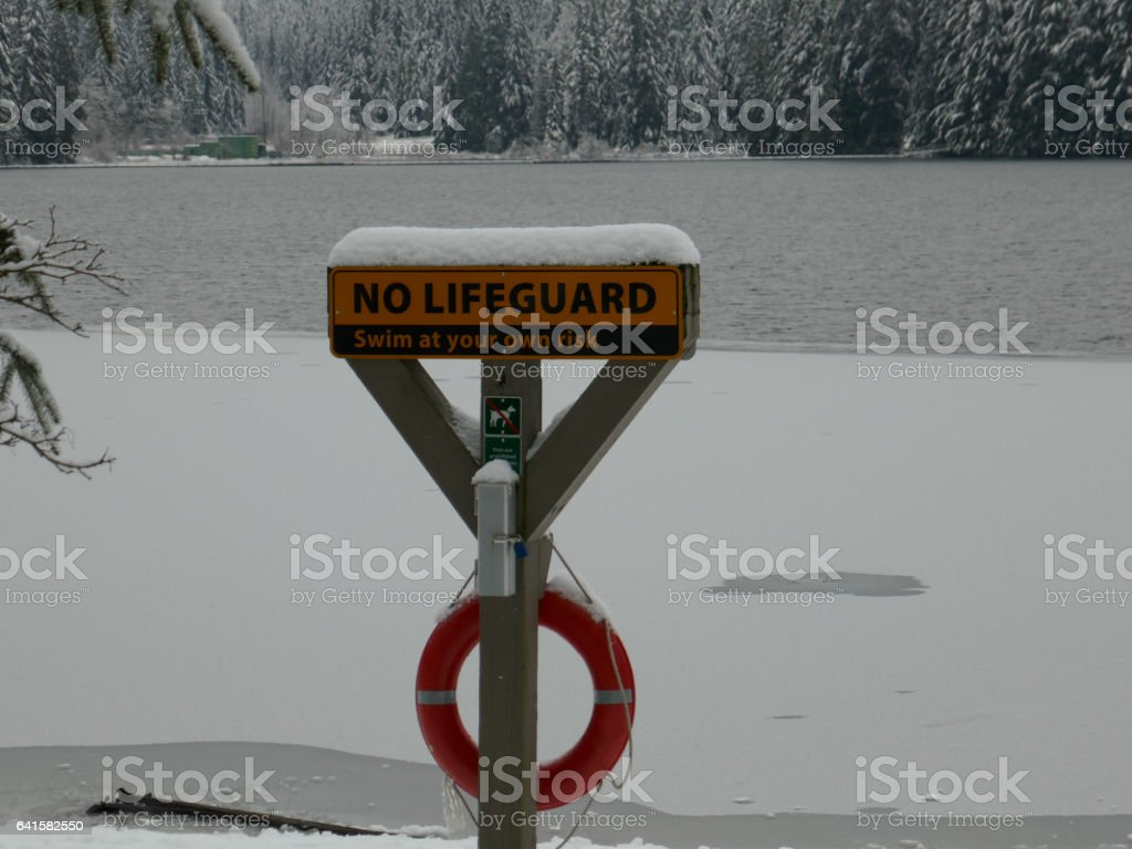 No Lifeguard sign on a frozen beach stock photo