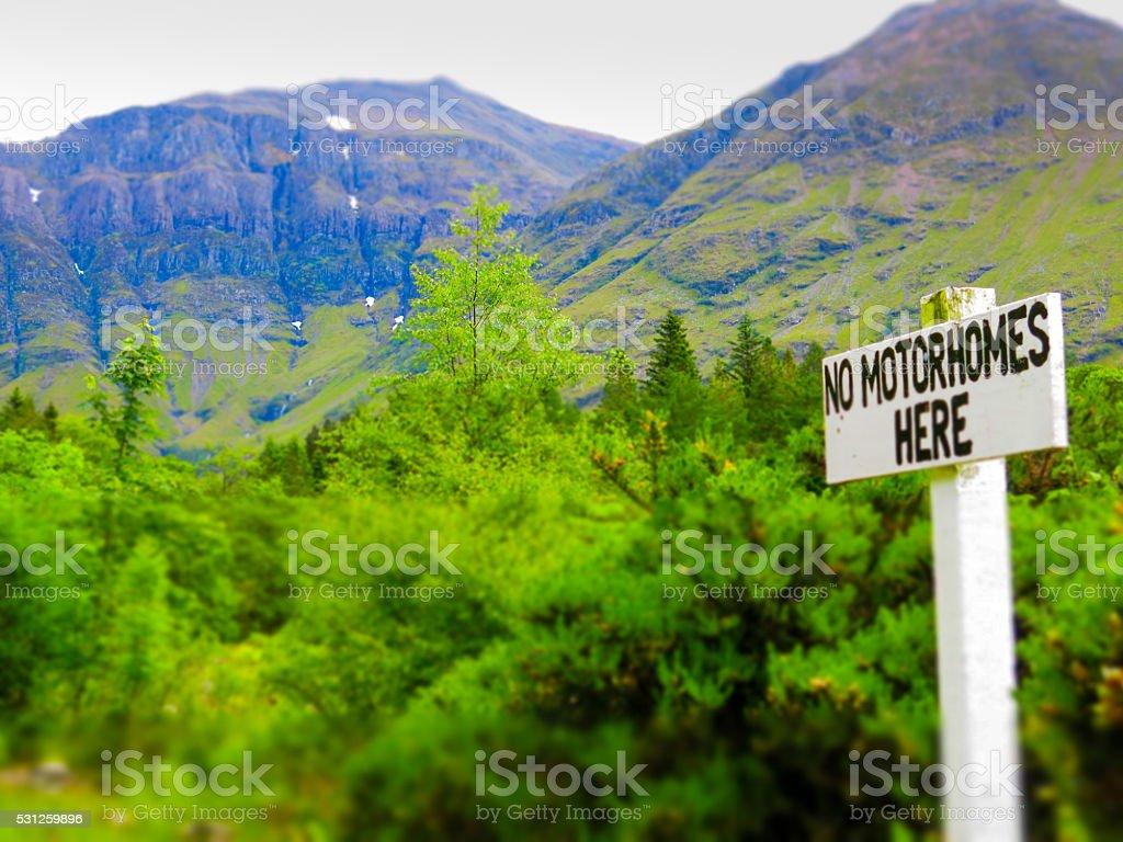 No Motorhomes Here Sign near Trees and Glencoe Mountains Scotland stock photo