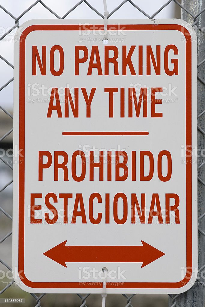 A no parking sign written in English and Spanish stock photo