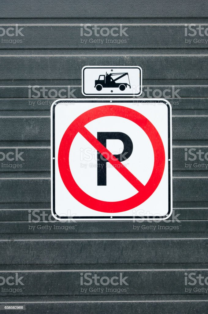 No parking tow away zone sign on a black garage door stock photo