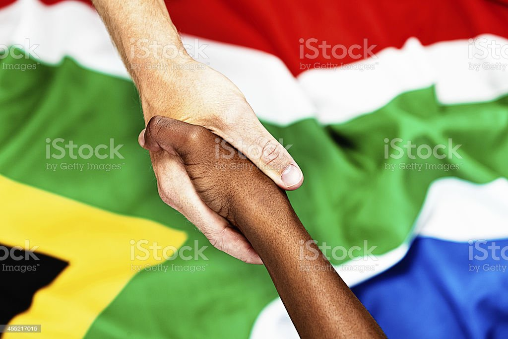 No racial tension here: interracial handshake on South African flag royalty-free stock photo