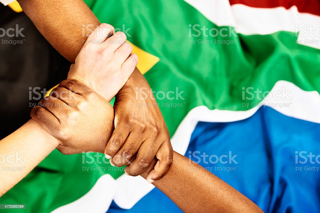 No racial tension here: triple handclasp on South African flag royalty-free stock photo