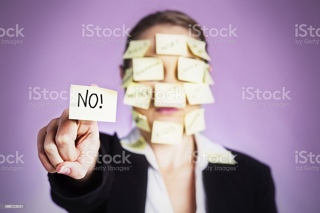 No! Says over-burdened woman covered in task reminders royalty-free stock photo