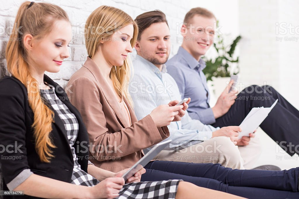 Group of friends sitting by wall in office. Pretty girl texting a...
