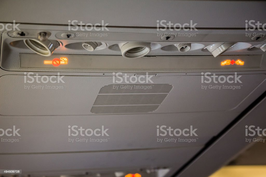 No Smoking and Fasten Seatbelt sign Inside an airplane stock photo
