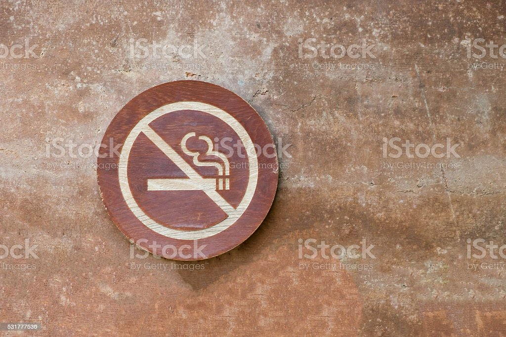 no smoking label on brown cement wall stock photo