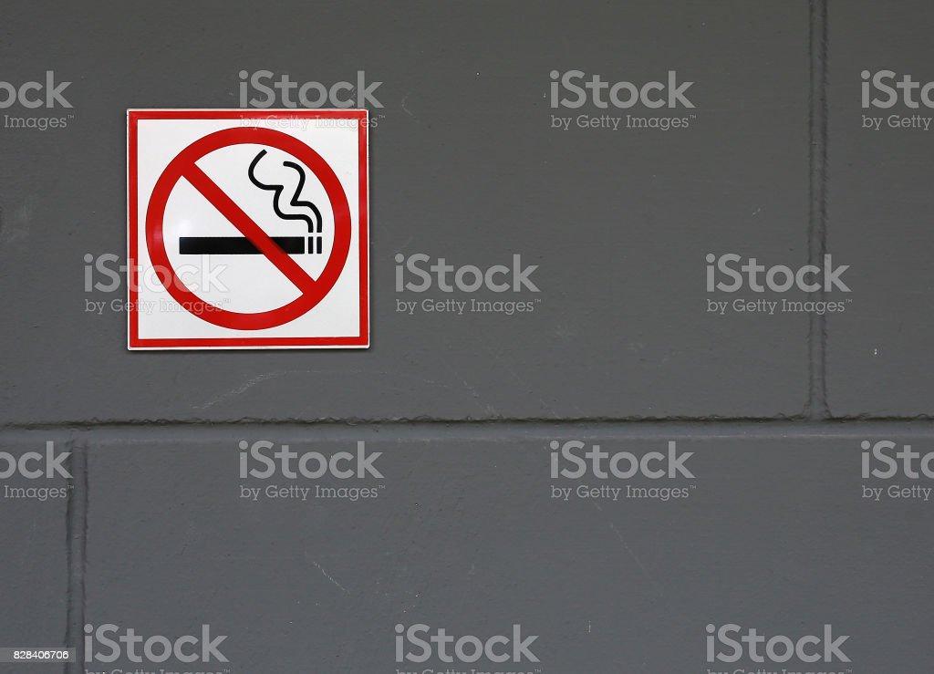 No smoking sign on the grey brick wall. stock photo