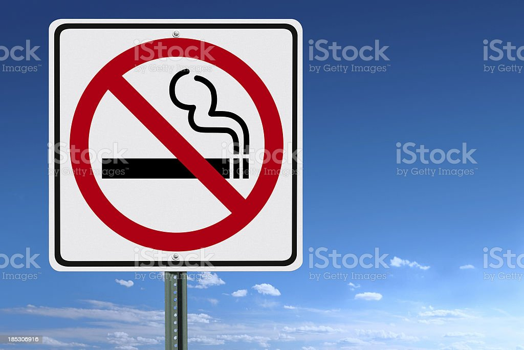 No Smoking Sign Post Over a Blue Sky Background stock photo