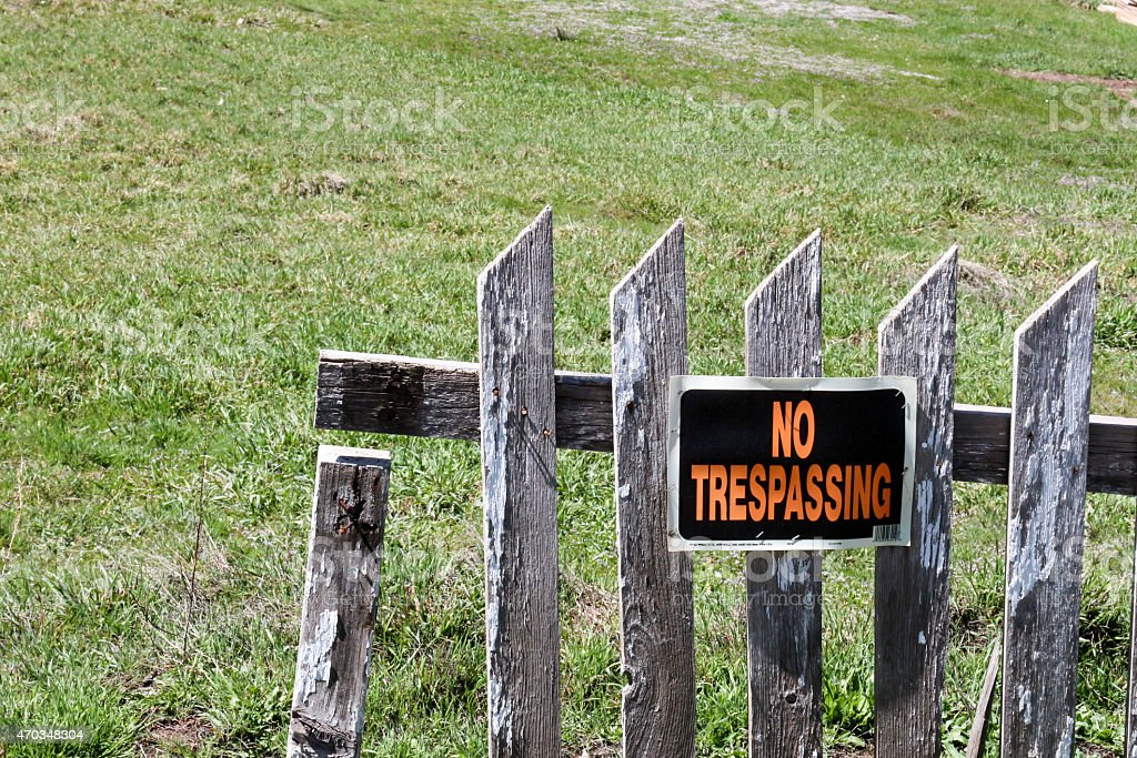 No Trespassing sign on a damaged, weathered picket fence stock photo
