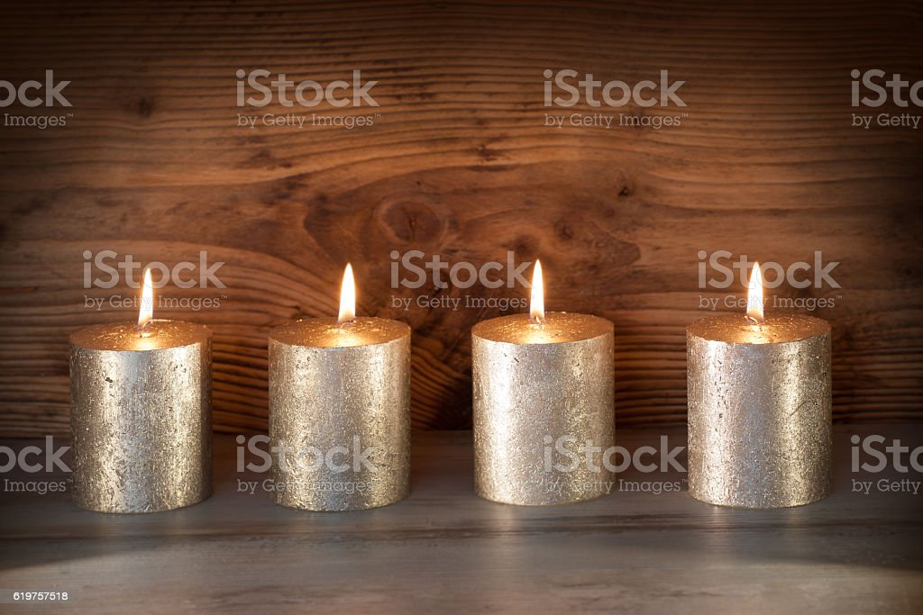 Noble candles against a background of wood stock photo