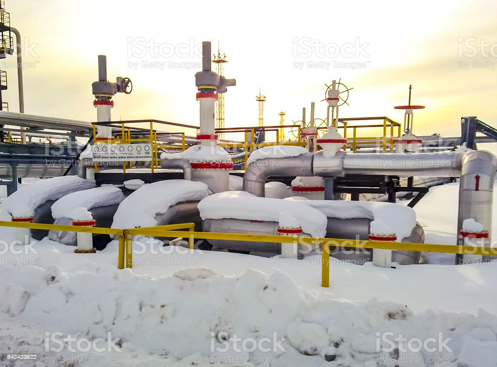 Node of valves on oil pipelines. Stop valves in the snow. Reducers on the valves. stock photo