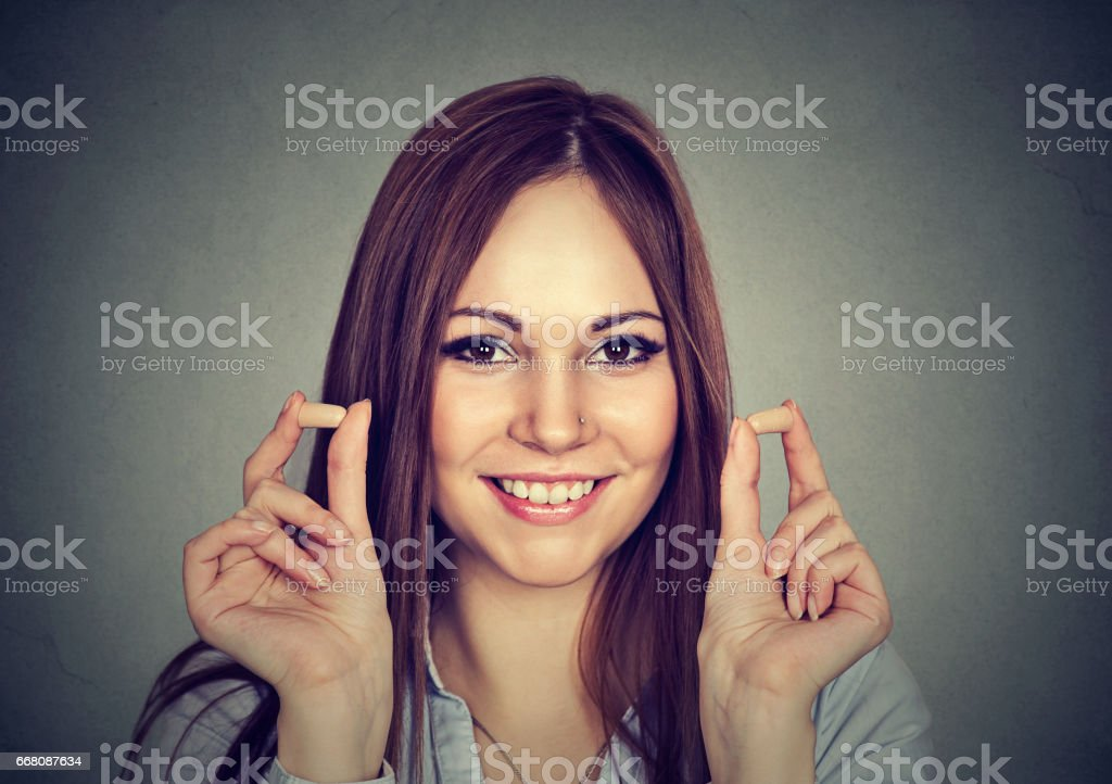 Noise control. Portrait young woman holding ear plugs stock photo
