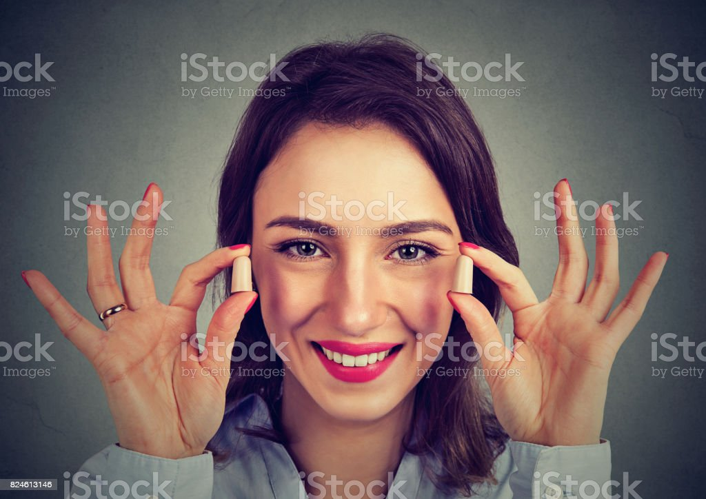 Noise control. Woman holding ear plugs isolated on gray wall background stock photo