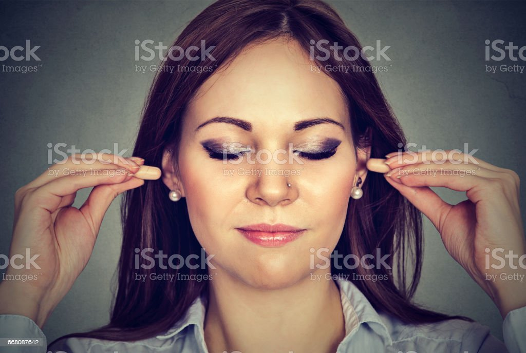 Noise control. Young woman with ear plugs stock photo