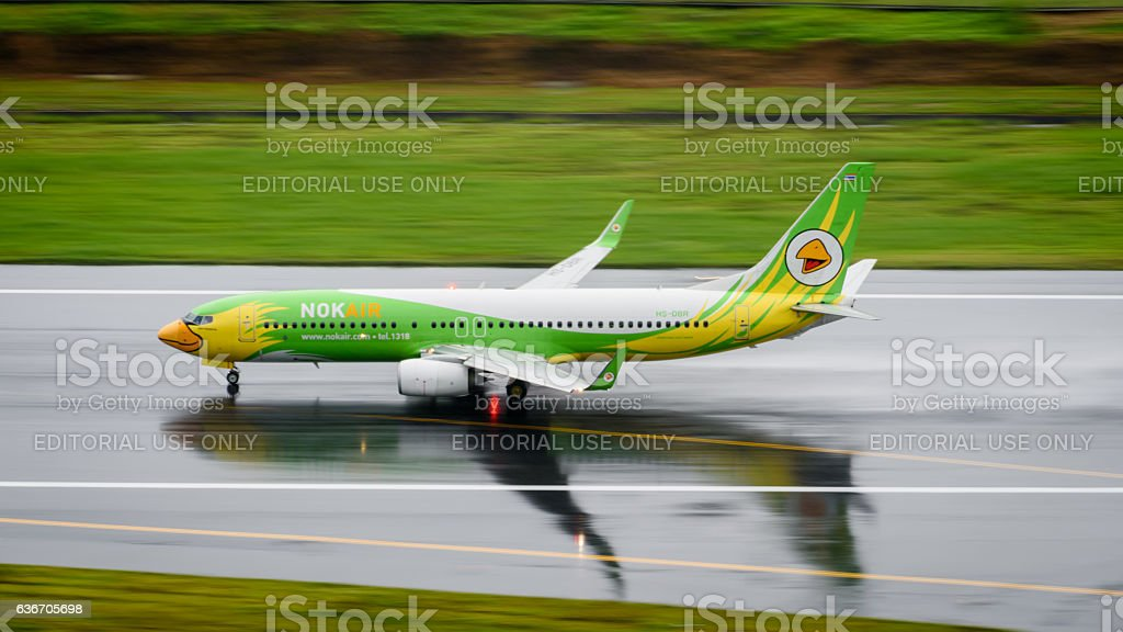 Nok air take off from phuket on wet runway stock photo