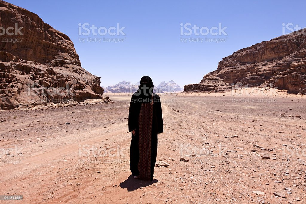 Nomadic woman with burka in the desert royalty-free stock photo