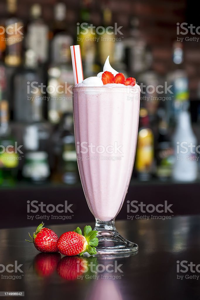 non-alcoholic strawberry milkshake cocktail on the classic black bar table royalty-free stock photo