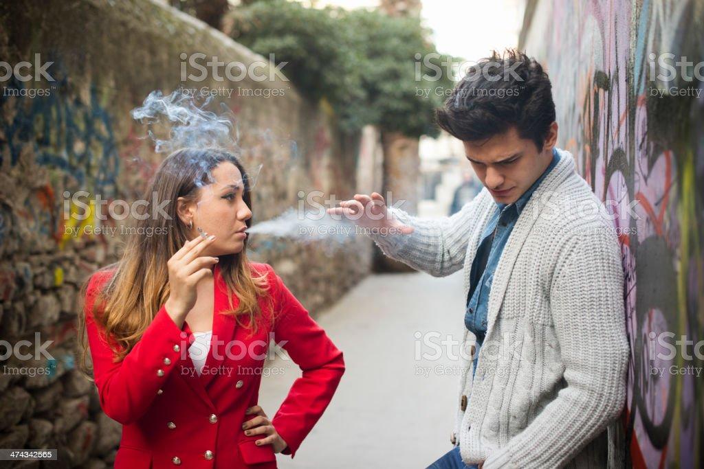 Nonsmoker Man and Smoker Young Woman stock photo