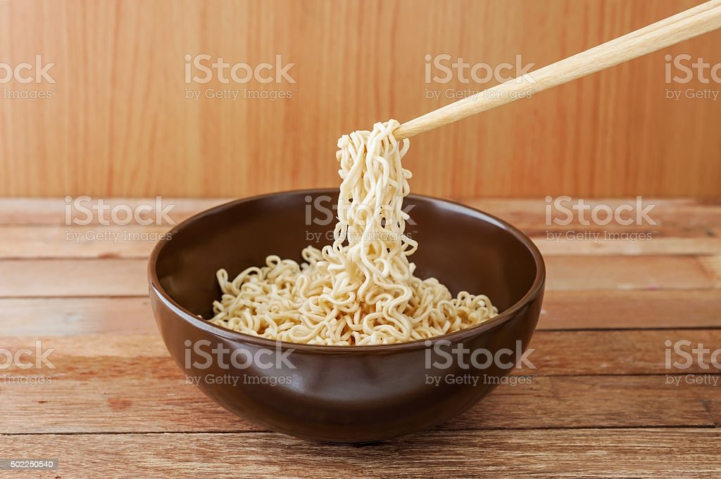 Noodle in brown bowl with wooden chopsticks stock photo