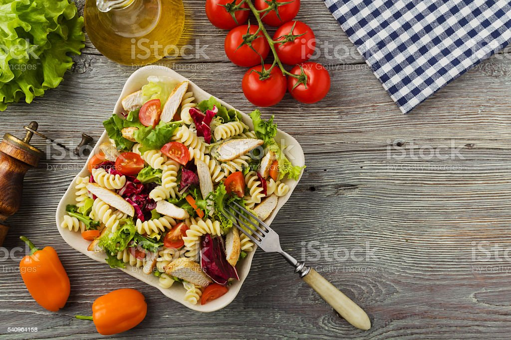 Noodle salad with green salad, tomatoes and roasted chicken. stock photo
