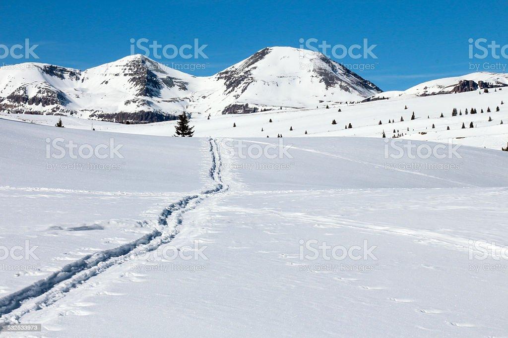 Nordic ski track through snow to peaks stock photo