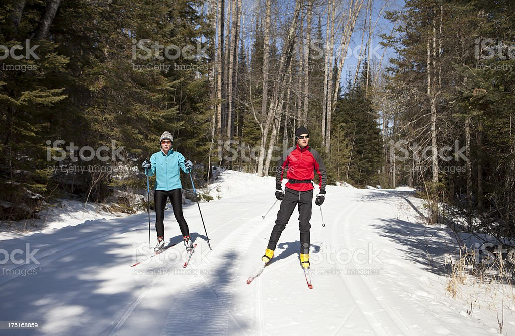 Nordic Skiing Couple Skate Skiing on a Groomed Trail. stock photo