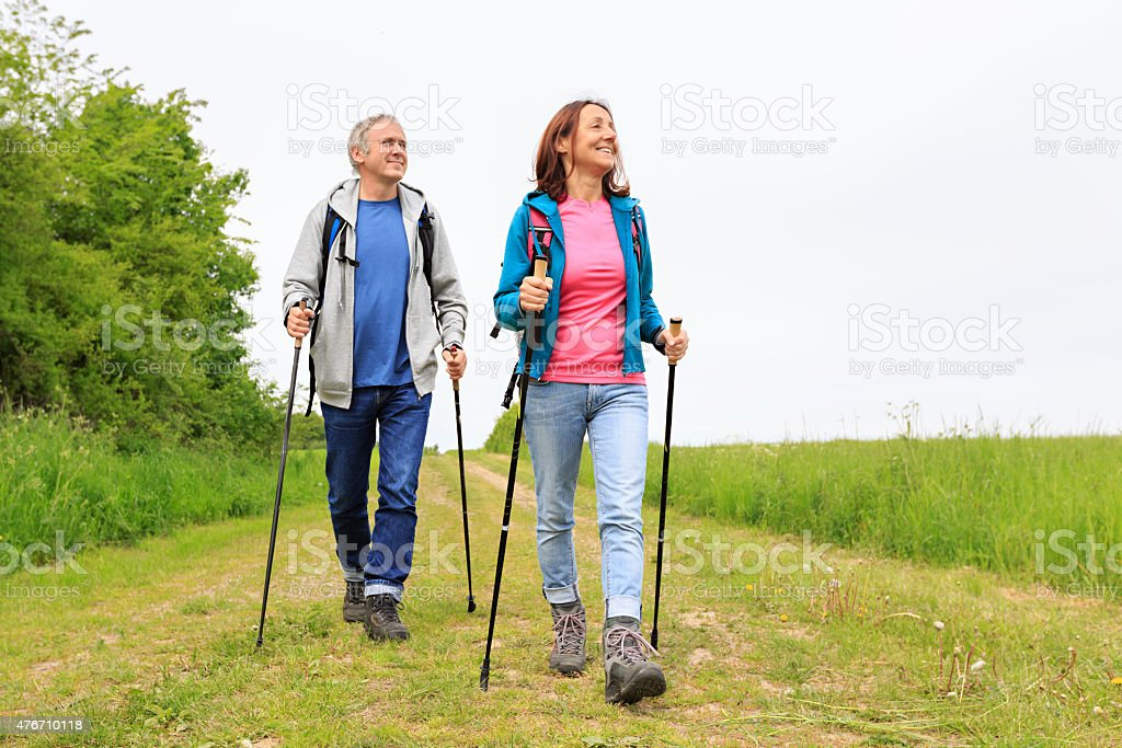 Nordic walking - active mature couple enjoying hiking stock photo