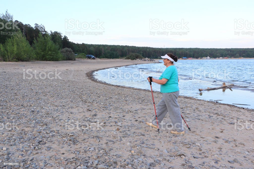 Nordic Walking - elderly woman is hiking along the river in the evening stock photo