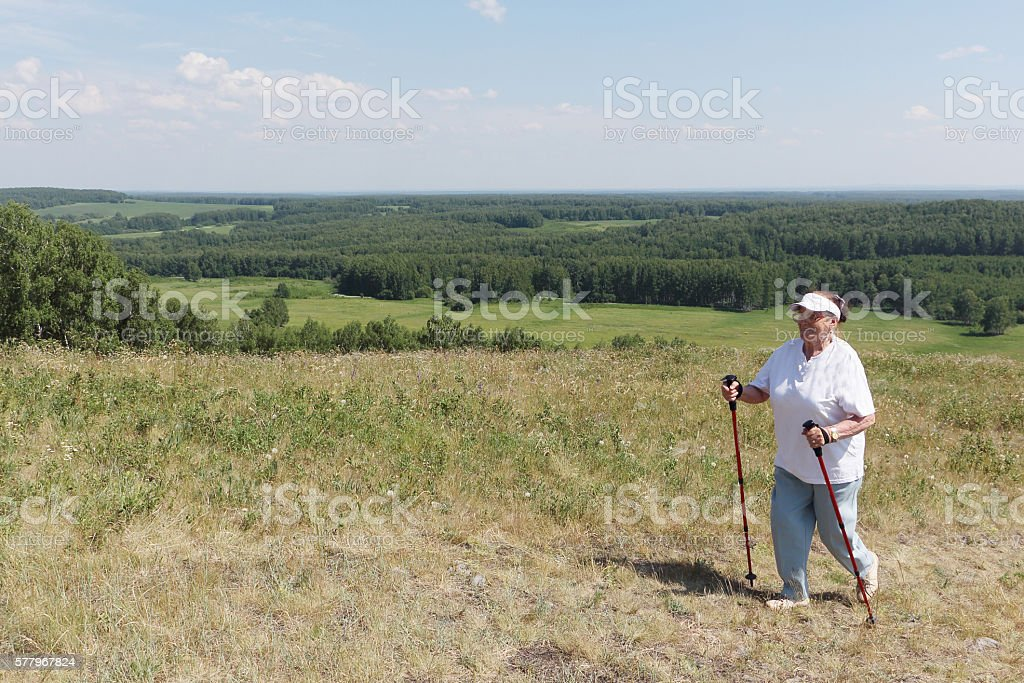 Nordic Walking - elderly woman is hiking  in the summer stock photo