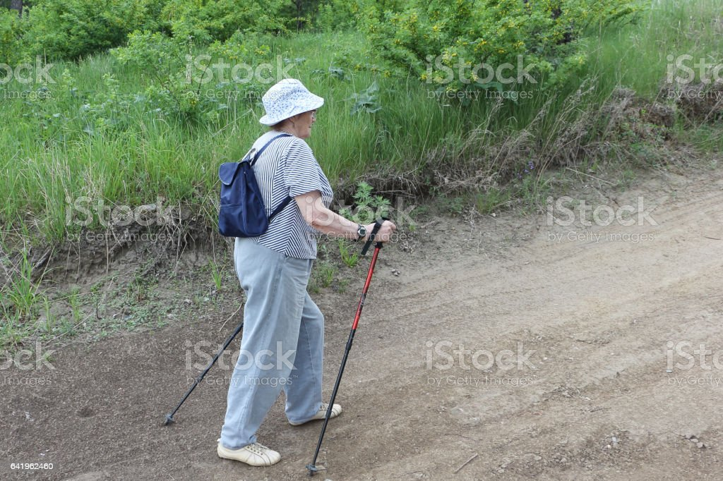 Nordic Walking-elderly woman in a striped blouse going uphill stock photo