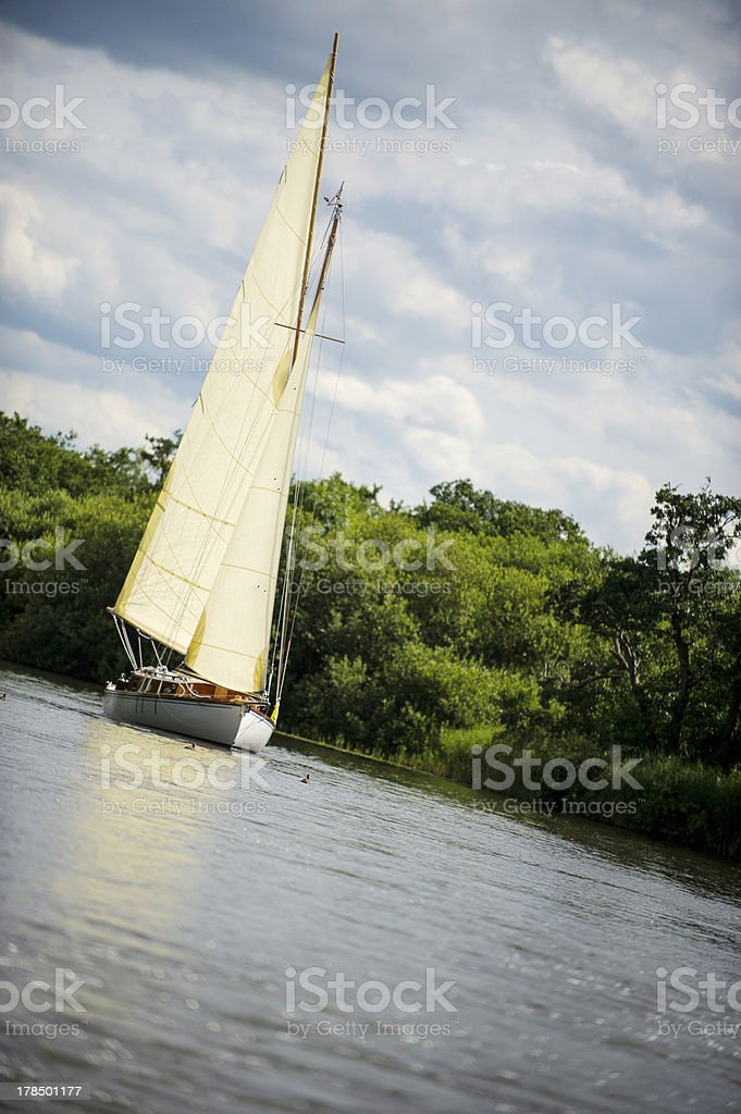 Norfolk Broads sail boat sailing down a river royalty-free stock photo