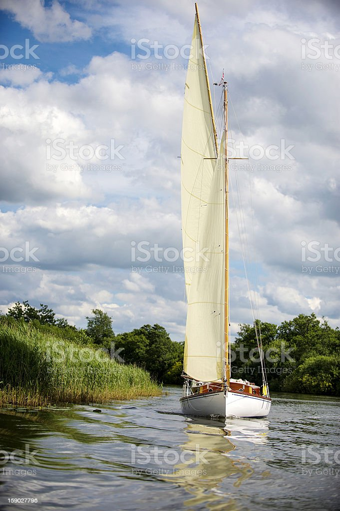 Norfolk Broads sail boat sailing on a river royalty-free stock photo