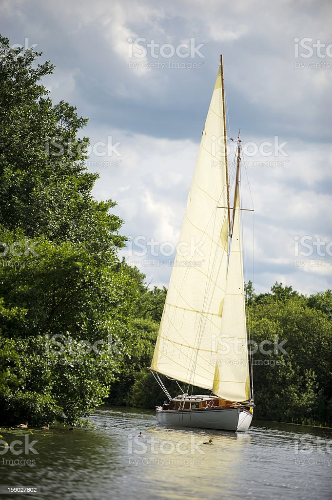 Norfolk Broads sail boat sailing on a river royalty-free stock photo